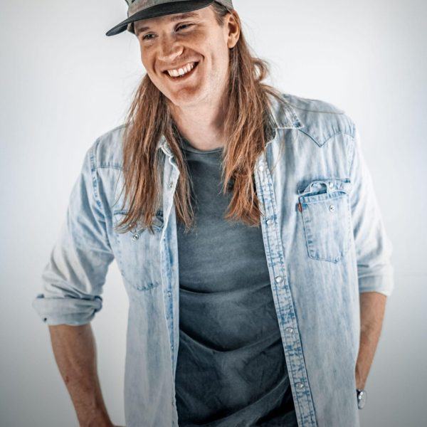 Texas artist Dustin Massey smiles and stands with hands in back pockets